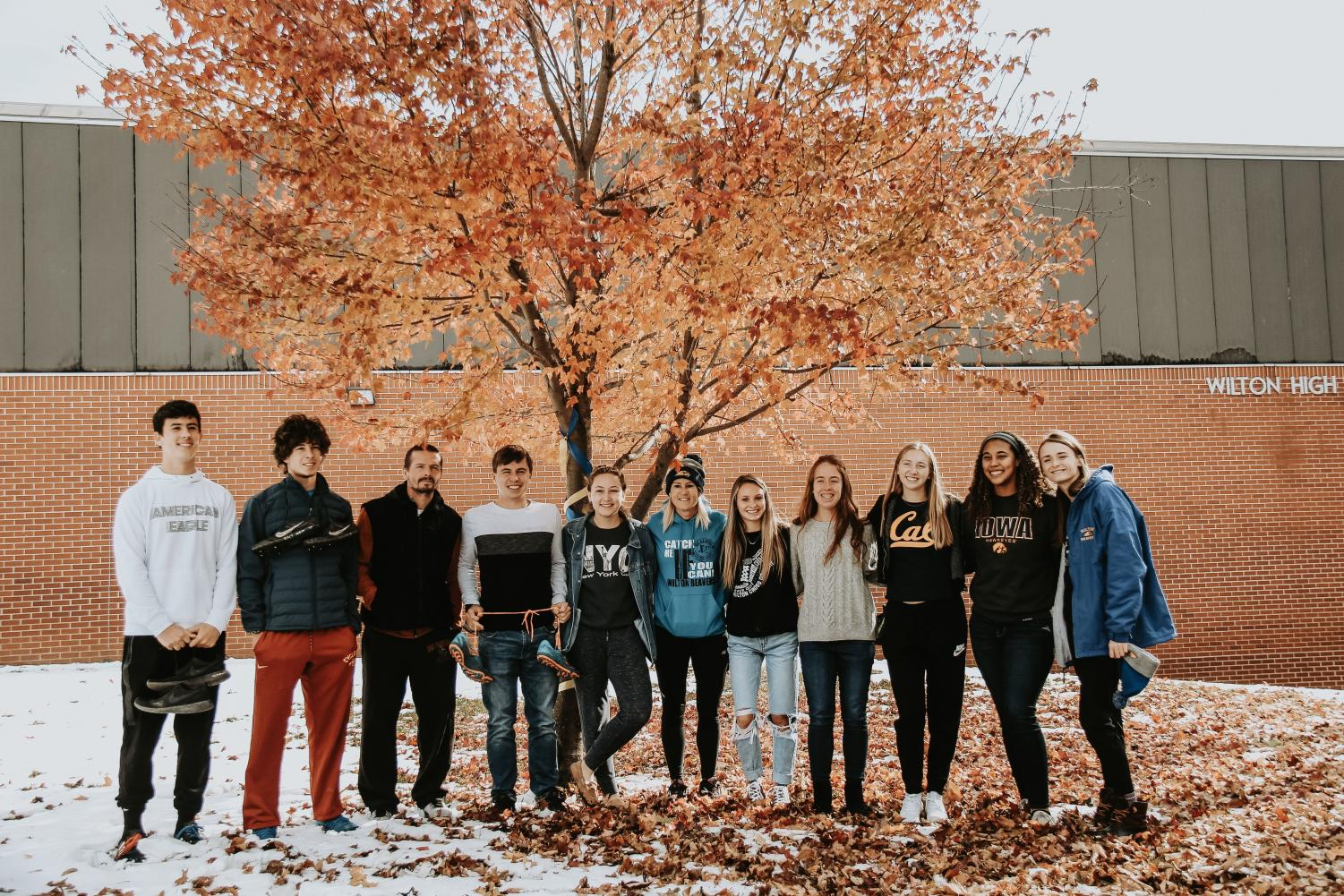 Senior cross country members and coaches pose outside of the new shoe tree